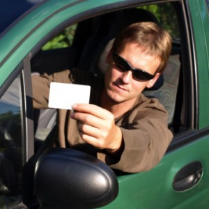 Man showing driver's license while sitting in car