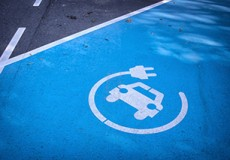 Logo 'charge your electric car here' on asphalt