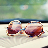 Elegant fashionable plastic women's sunglasses on interior car dashboard.